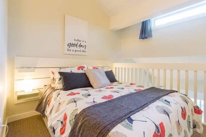 Main sleeping area with queen sized bed in open loft space.