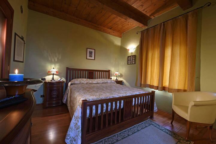 Vista della camera matrimoniale con pavimenti e soffitto in legno