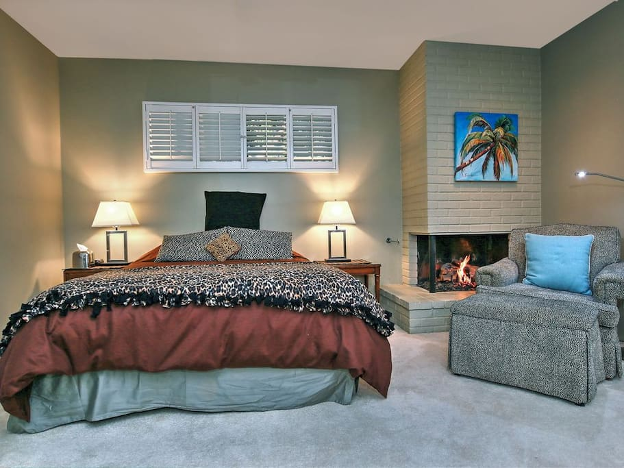 A luxurious queen bed & comfy chair for enjoying the fireplace