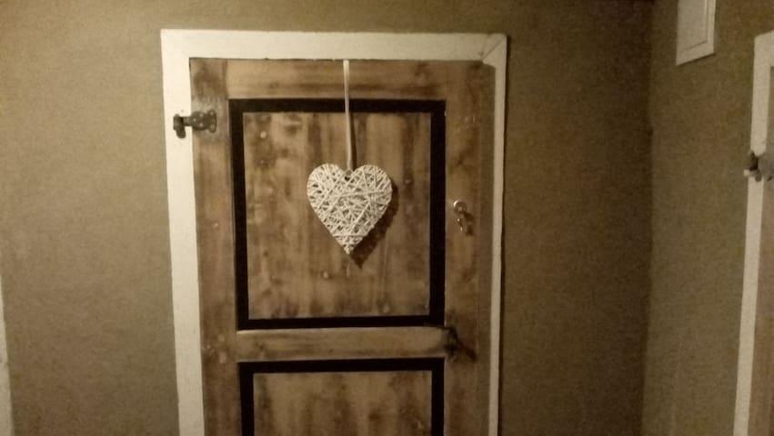 Der Flur ist mit Naturlehm verputzt. Hier durch die neu abgebeizte Tür geht es in ihre Wohnung. Der Schlüssel steckt in der Tür und ist für die Wohnung und für die Haustür.