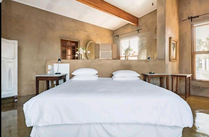 Bedroom with open bathroom behind
