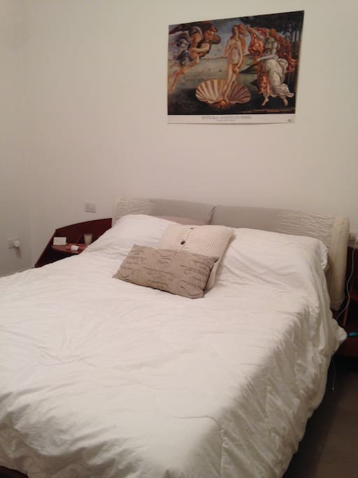 Bedroom with queen sized bed and plenty of storage space, plus a balcony overlooking the street