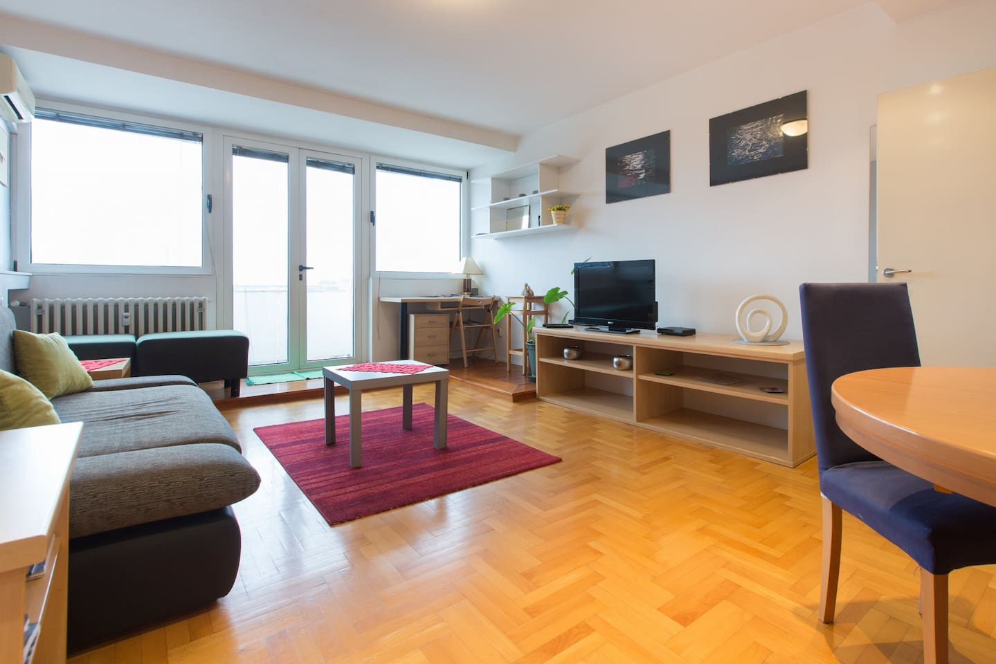 Living room with double sofa bed, tv, working area and baalcony