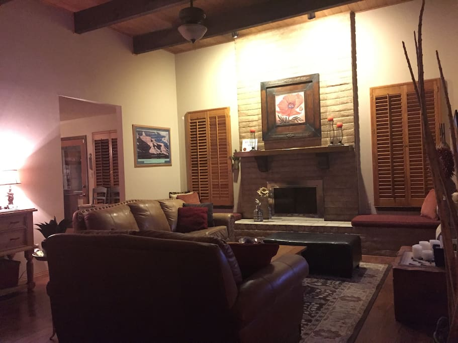 """Summer Pic: Cozy living space with 60"""" television and wood-burning fireplace for cool evenings."""