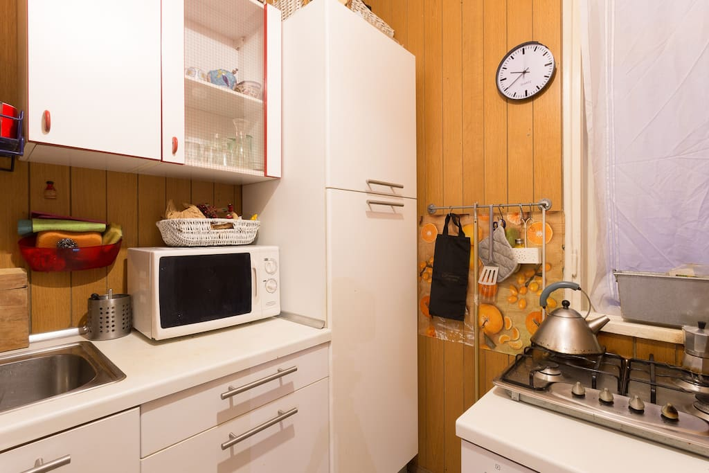 small kitchen with fridge, oven and gas stove