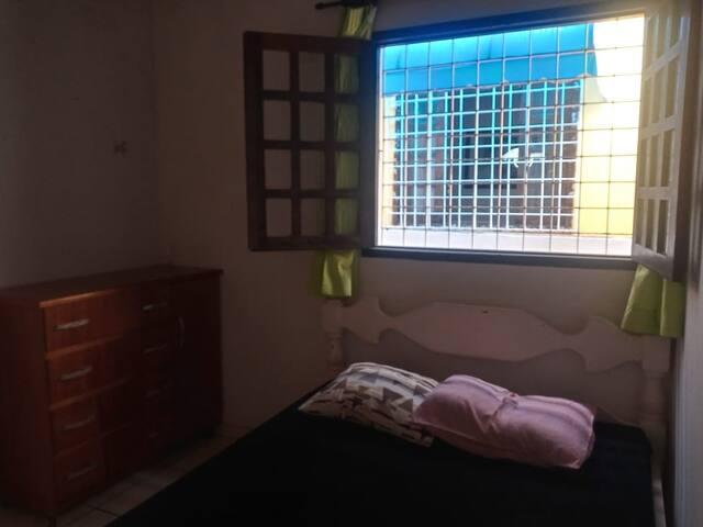 Quarto 2 com ventilador de teto, cama de casal e cômoda para guardar os pertences pessoais.