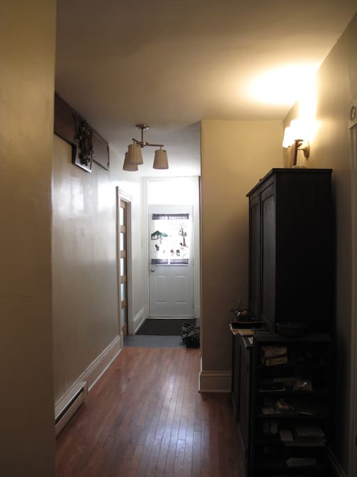 Room is at the front of the house. Long hardwood halway with antiques