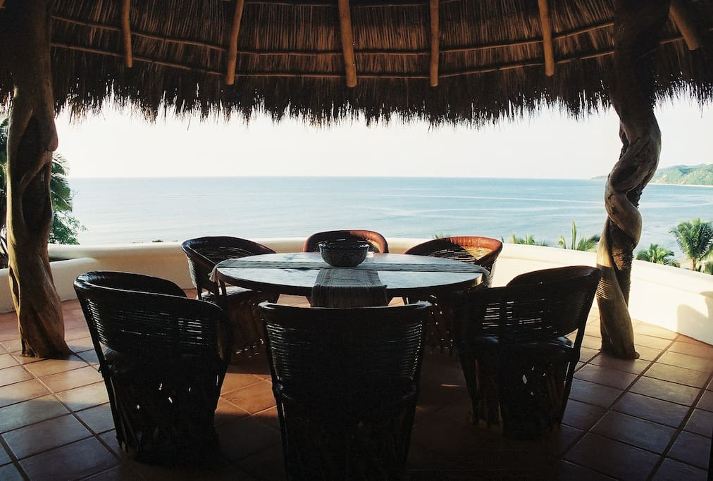 Large equipali table for alfresco dining under a traditional palapa on the patio