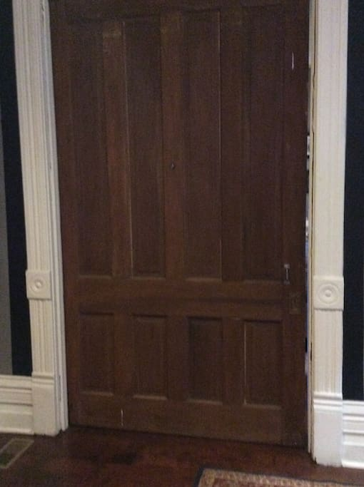 """Enter your room through a large pocket door in the main entry hall into  what was once the """"parlor"""" ."""
