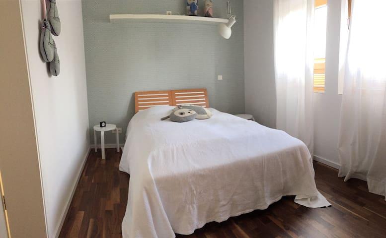 kleines blaues Schlafzimmer mit schmalem Doppelbett