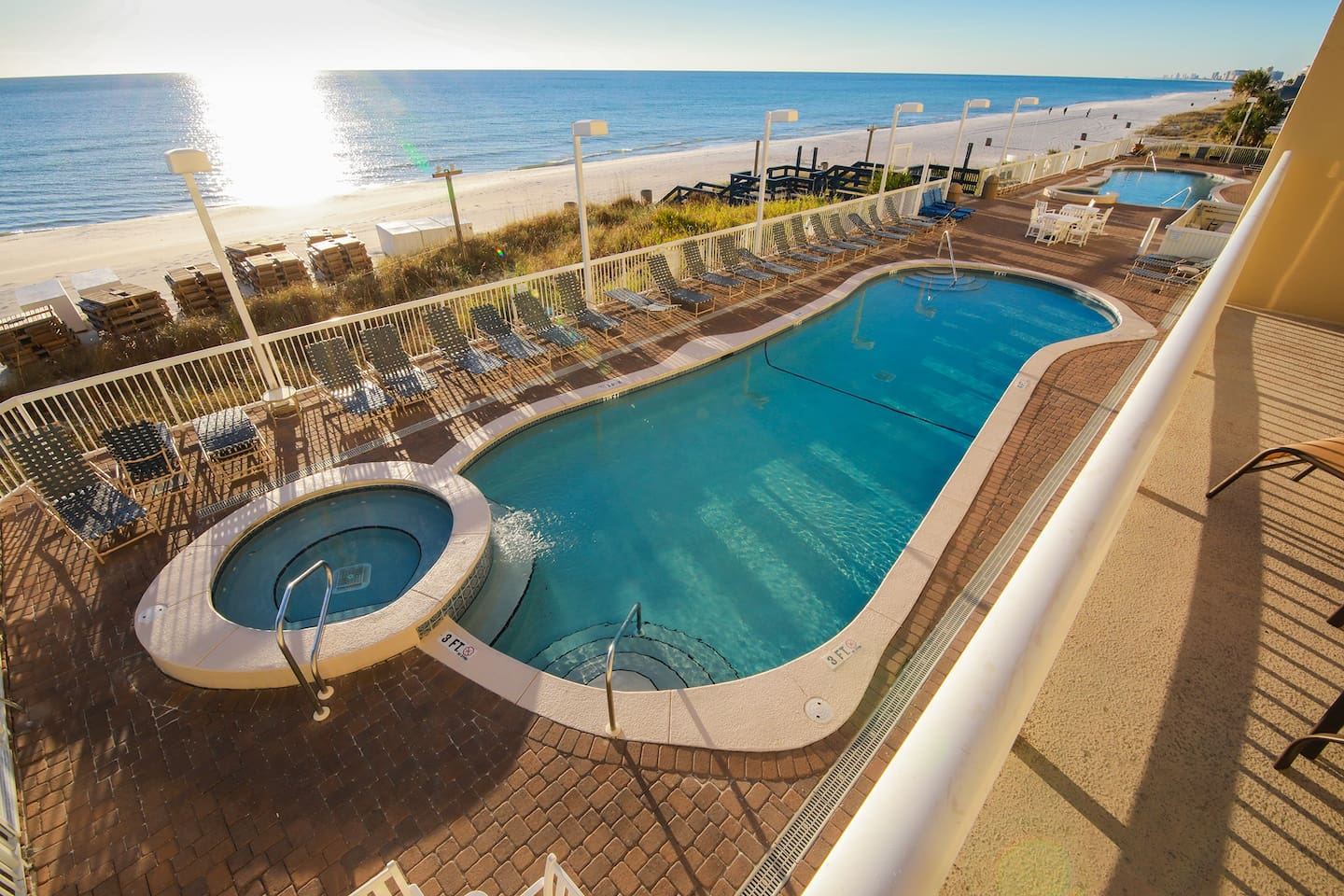 Yes, this can be YOUR vacation view!  Sundeck and Two Pools with hot tubs, one on each side of the building.