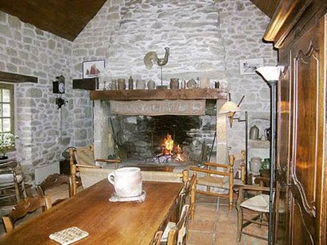 La pièce principale: une salle à manger avec sa grande table en bois massif et son petit salon devant l'âtre breton traditionnel. Sur la gauche, l'accès à la cuisine et à la salle de bain.