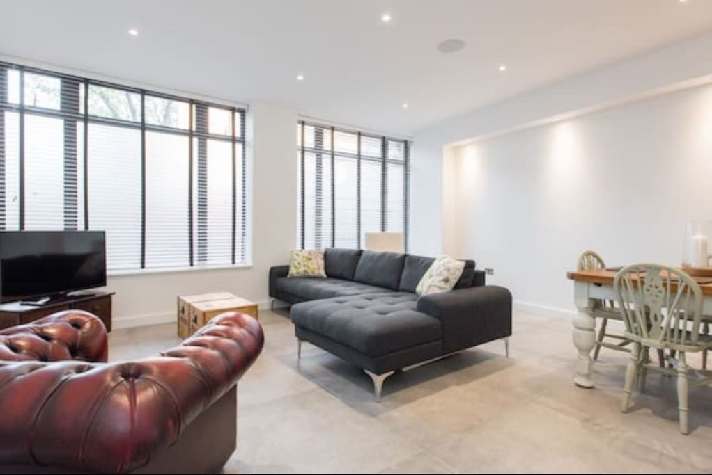 Spacious living room with large comfy l-shaped sofa, underfloor heating and speakers in the ceilings.