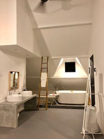Duplex suite top floor basin and bathtub corner.