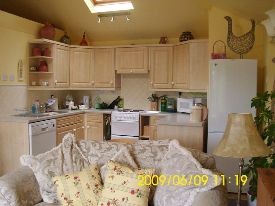 Fitted kitchen with dishwasher, electric cooker, microwave oven and large fridge freezer.