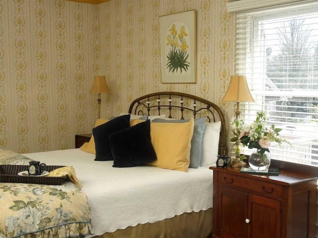 One of our most popular rooms! You'll see why as you bask in this sunny room's elegance. Relax in front of the original fireplace, but you'll LOVE the grand brass bed!