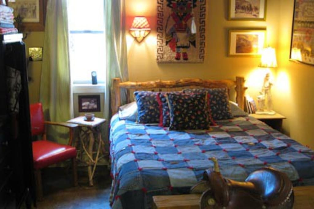 Cowboy Dreamland:  Log bed, custom denim comforter, Mexican saddle, red leather chair and western art
