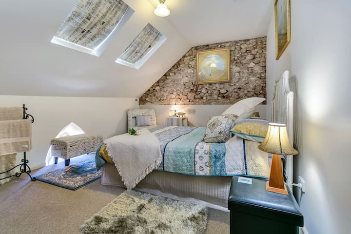 BEDROOM 2 is located upstairs & offers a double bed, hanging hooks on the back of the door, ceiling fan & oil heater.