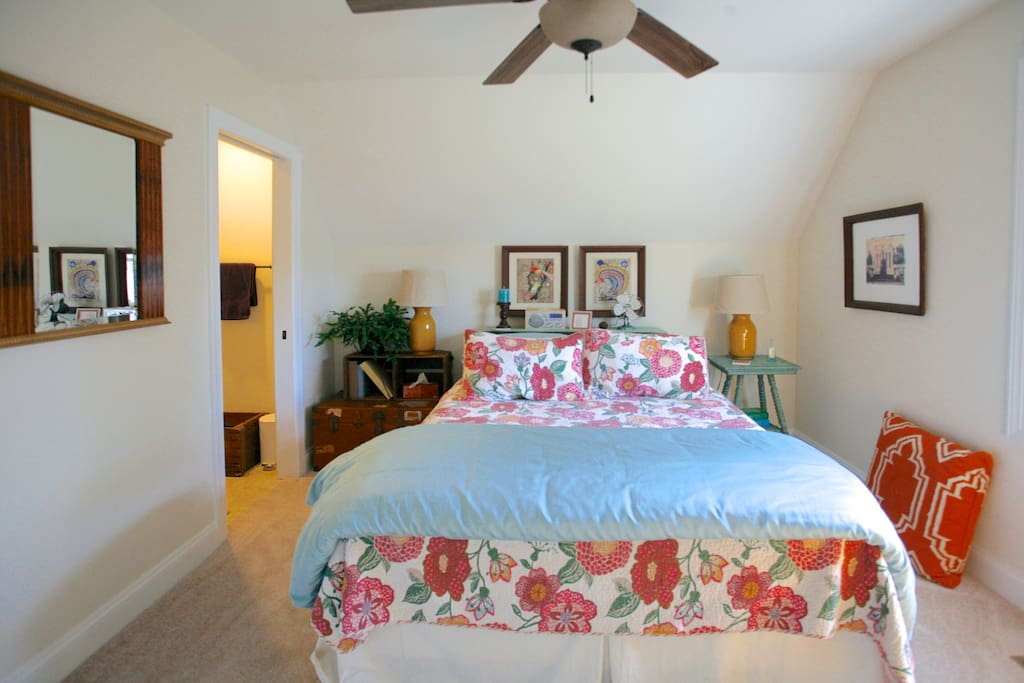 Queen size bed in guest room with ceiling fan