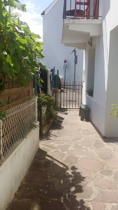 Vue depuis l'entrée du studio sur la rue. Voici le petit portail rouge par lequel vous entrez dans la maison familiale