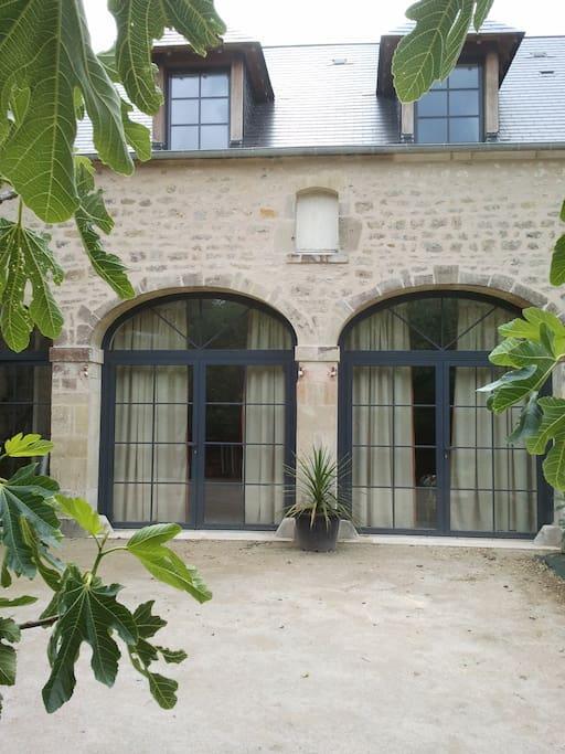 Façade du XVIIème avec grandes baies vitrées ouvrant sur le séjour