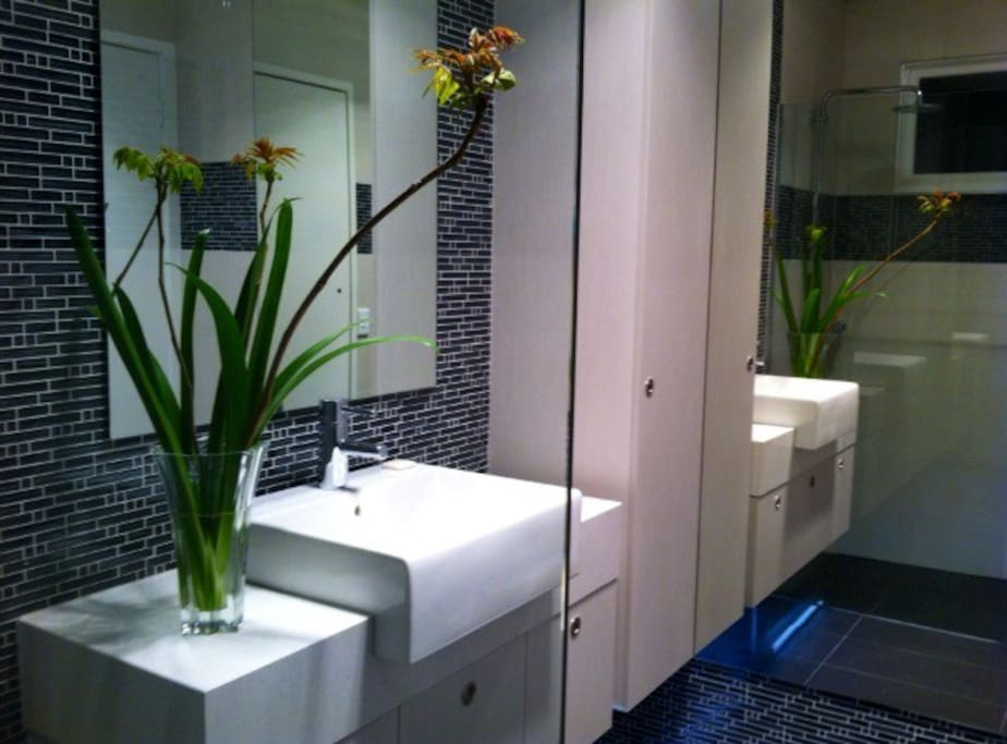 The bathroom is spacious, with a walk-in European hand-held & rain shower for total indulgence