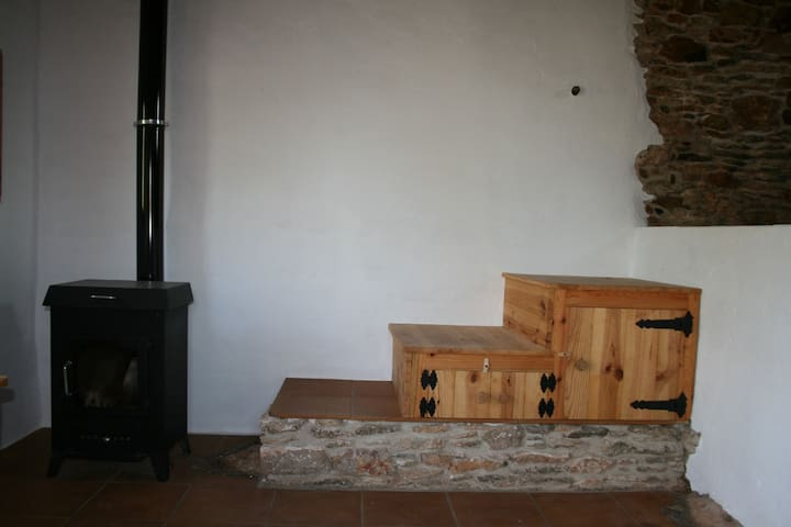 log-burning stove and steps/cupboards up to the mezzanine