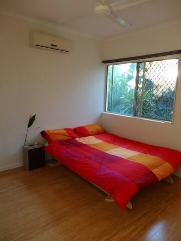 Smaller bedroom has futon bed, wardrobe, air conditioning and big window