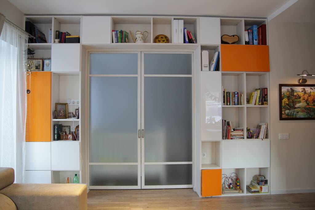 Шкаф в гостинной с раздвижными стеклянными дверьми в спальню