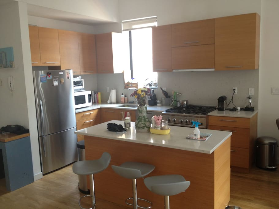Open kitchen with professional appliances including microwave and toaster oven