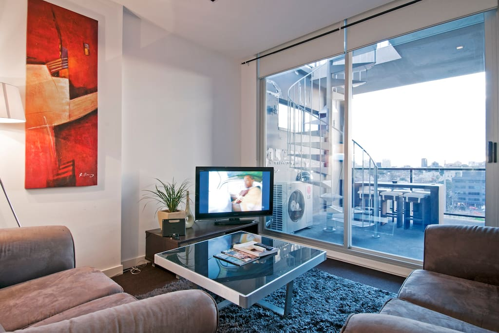 Comfy couches and large LCD TV, dvd player, iphone dock and WIFI broadband. Spiral staircase up to rooftop deck!