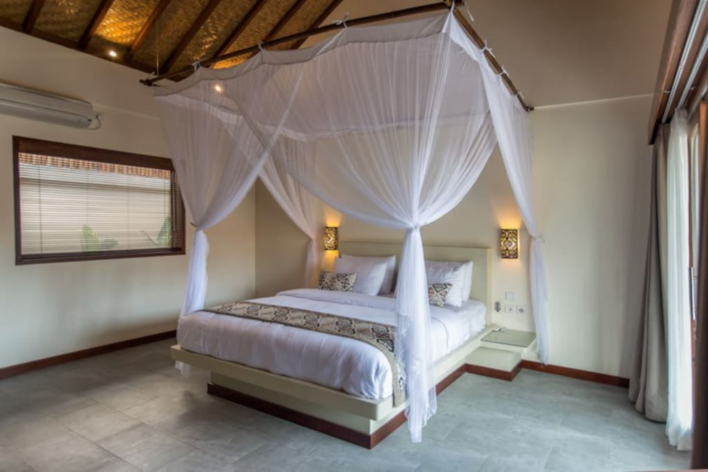 Room 2 overlooks the pool. King size bed, ac, fan, mosquito net. shares a large bathroom with room 1
