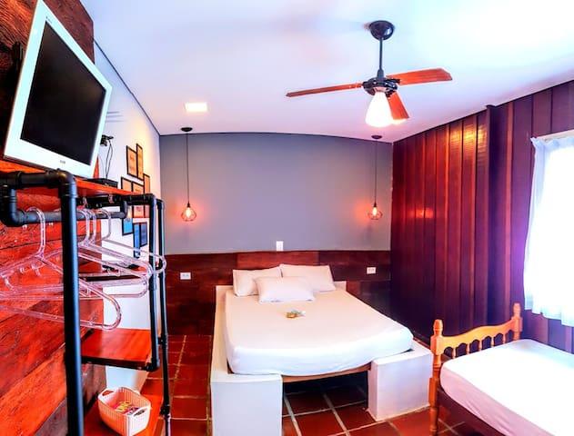 Quarto com televisão com suporte articulado, wi fi, 1 cama de casal, uma bicama, 1 beliche, arara de roupas com prateleira, ventilador de parede e ventilador de teto.