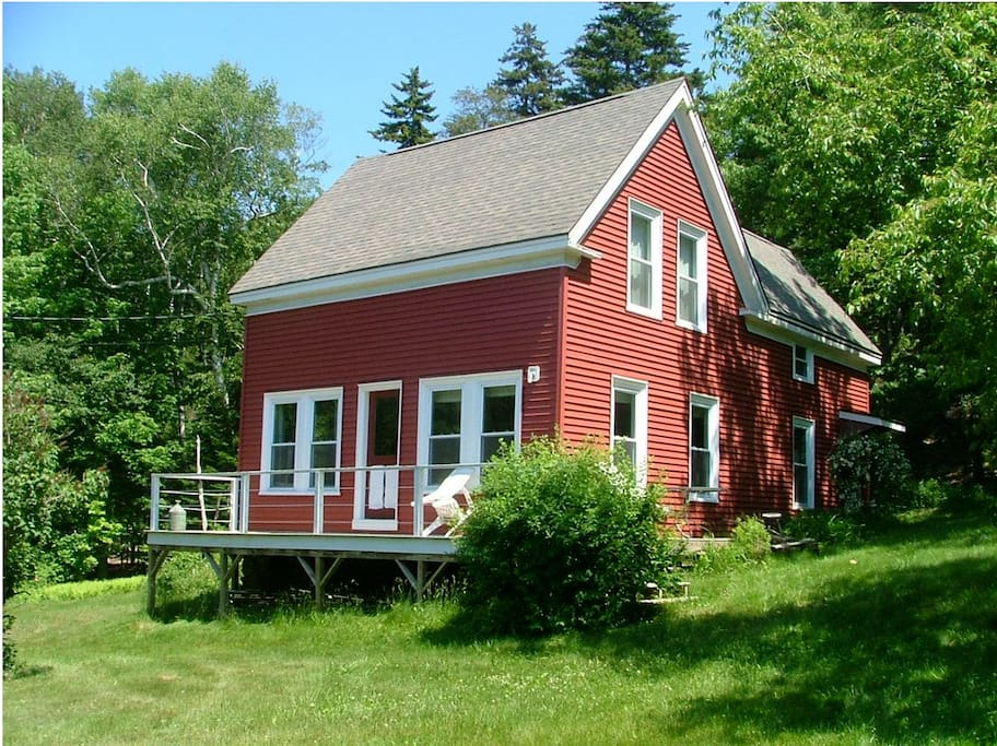 The Hedman Island house, back off the road, sitting against the pine forest, on a large green lawn.