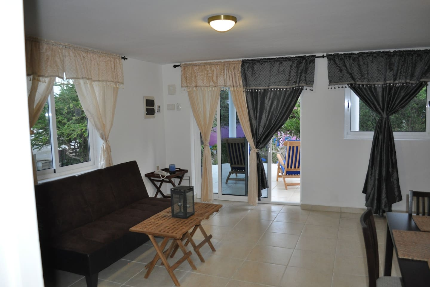 Open and breezy living room with adjoining porch with amazing view