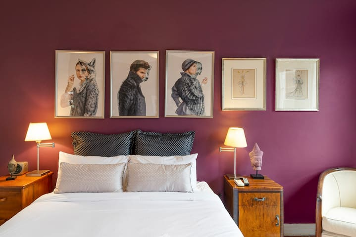 The plum accent wall in the master bedroom provides a pop of colour and a backdrop for the eccentric artwork to stand out.