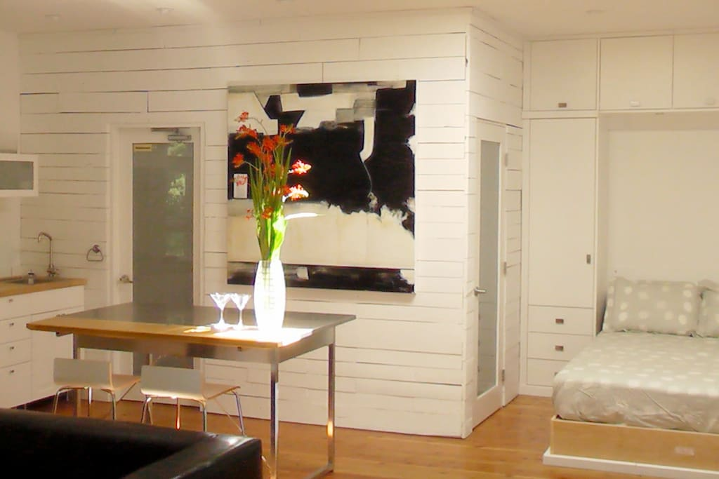 Comfy wall-bed, kitchenette, painting and dappled light from sky windows.
