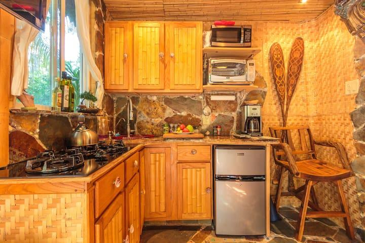 Kitchen with stove top & mini fridge.