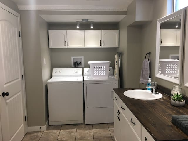 Washer and Dryer laundry area. Including detergent, dryer sheets, laundry basket, iron and ironing board.