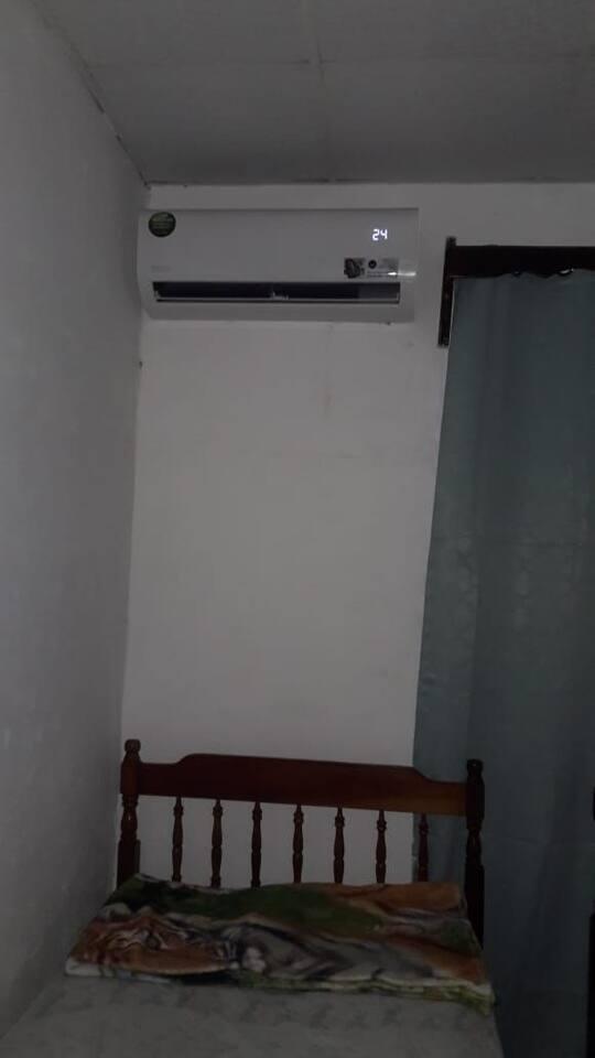 1 de las dos camas individuales con que cuenta la habitación y el aire acondicionado