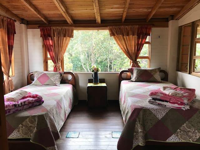 Habitación con camas dobles y vista al bosque y lago