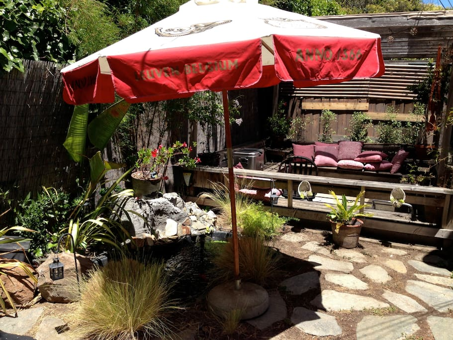 Backyard with gazebo and BBQ. Pond has been removed and replaced with drought-tolerant plants.