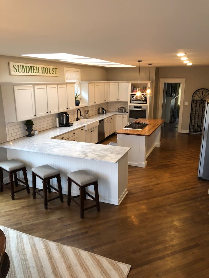 Newly renovated kitchen with marble counters, farmhouse sink and stainless steel appliances