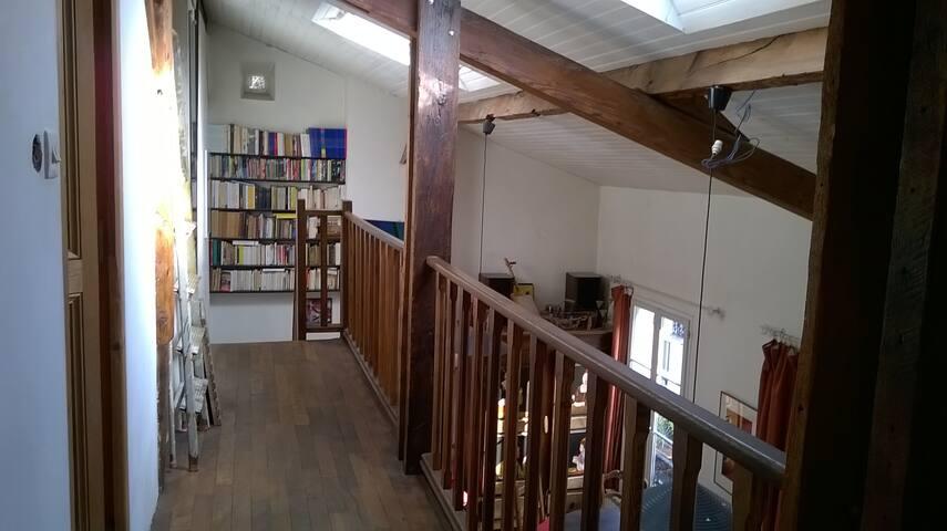 la galerie qui domine la pièce centrale et dessert 2 chambres et une salle de bain