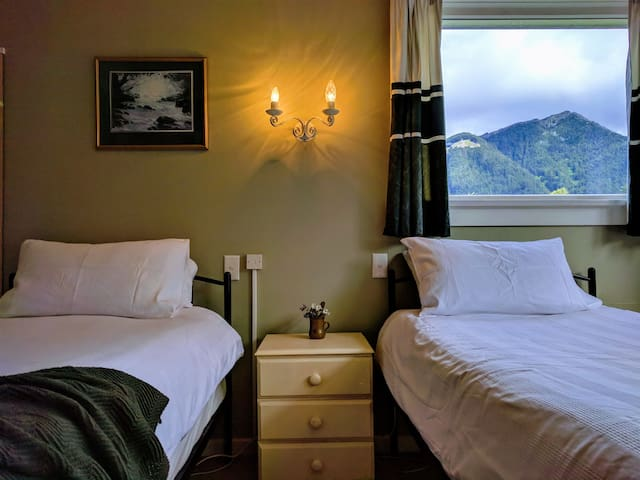 The twin bedroom has soft shades of green and blue to  complement the mountains and garden surrounding the cottage