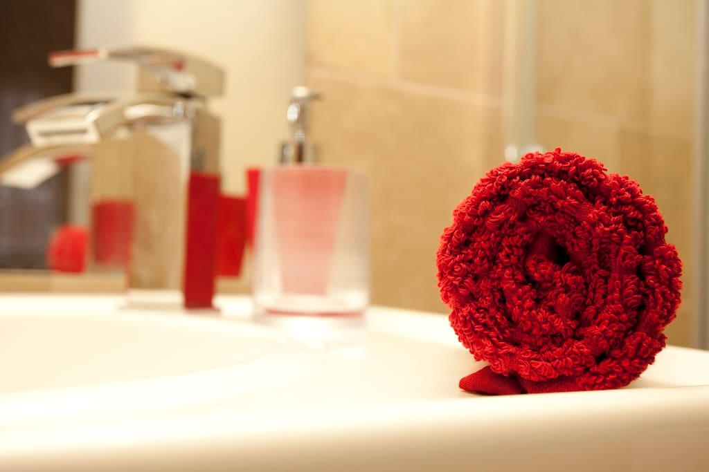 Modern bathroom with soft towels, shampoo, hairdryer and tasty applications