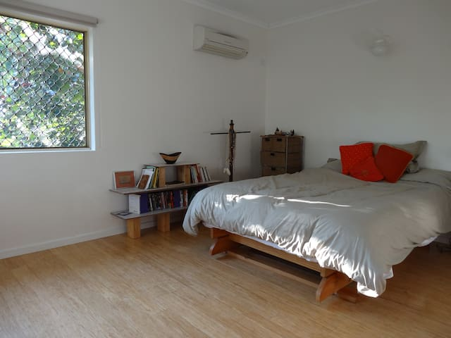 The master bedroom has two big windows looking out on tree tops