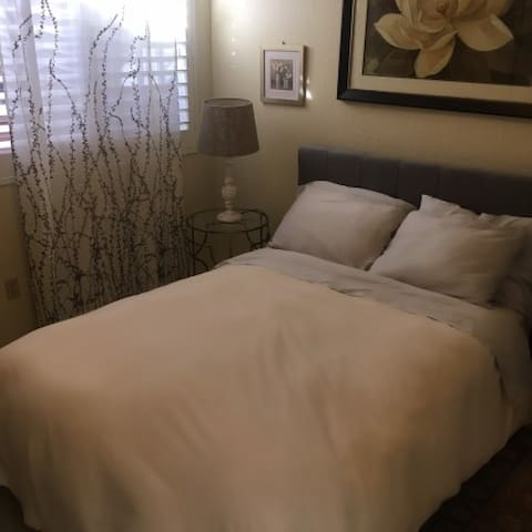 Guest bedroom with plantation blinds that can either fill the room with natural light or black out the room.