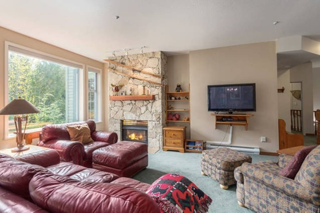 Open concept living room with gas fireplace and great natural light