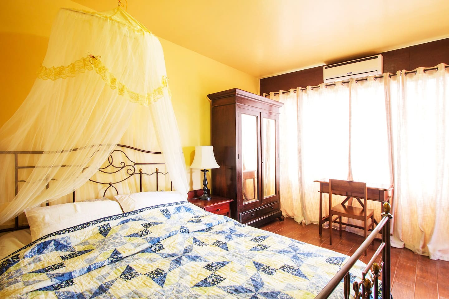 The Garden Room is furnished with a queen-sized bed and an air-conditioning unit.